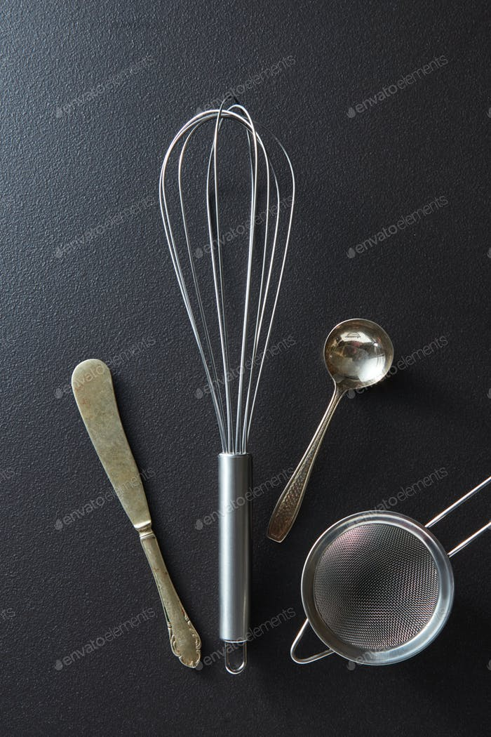 Set of kitchen tools knife, whisk, sieve and spoon on black concrete background with copy space. Top