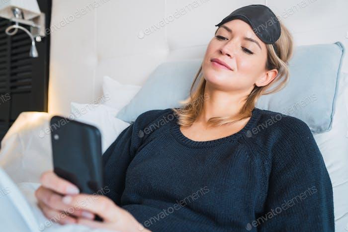 Junge Frau mit ihrem Telefon während der Liege auf dem Bett.