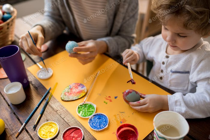 Little Boy Painting Easter Eggs with Mother