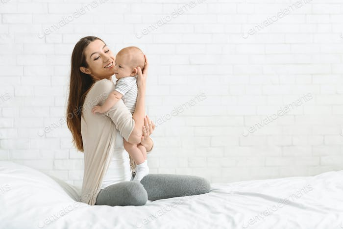 Happy millennial woman sitting on bed holding her baby son