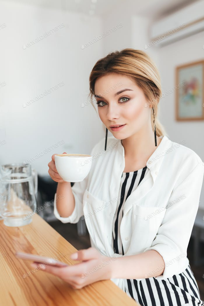 Pretty lady with blond hair sitting at the counter and drinking coffee in coffee shop