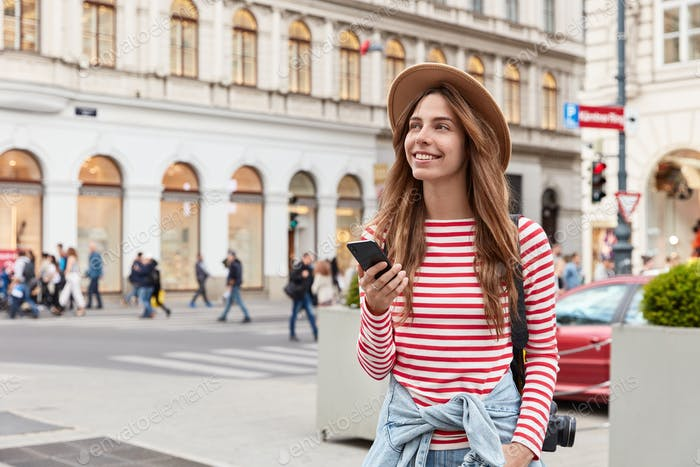 Cheerful woman enjoys walking in old city center, uses mobile phone app for navigation in unknown pl
