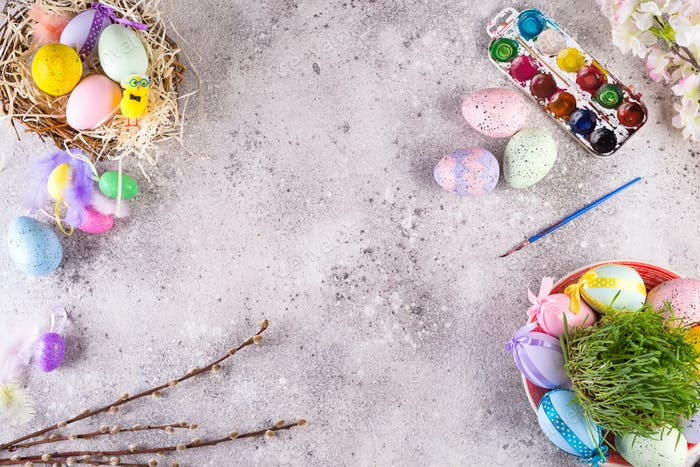 Easter eggs in a nest of grass, homemade glazed cookies and paints for painting eggs and grass