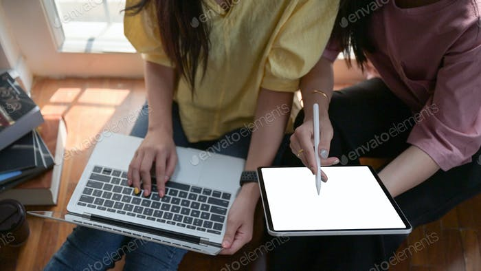 Female college students use a tablet and laptop study online at home to prevent Covid-19 outbreak.