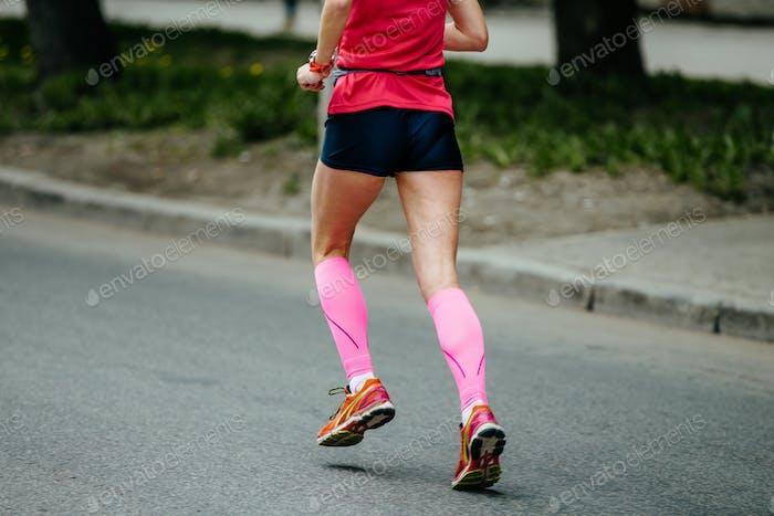 Rücken Läufer Mädchen in rosa Kompressionssocken