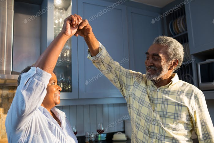 Affectionate couple dancing in kitchen