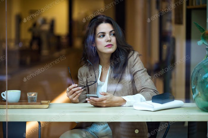 Concentrated young businesswoman texting with her mobile phone in the coffee shop.
