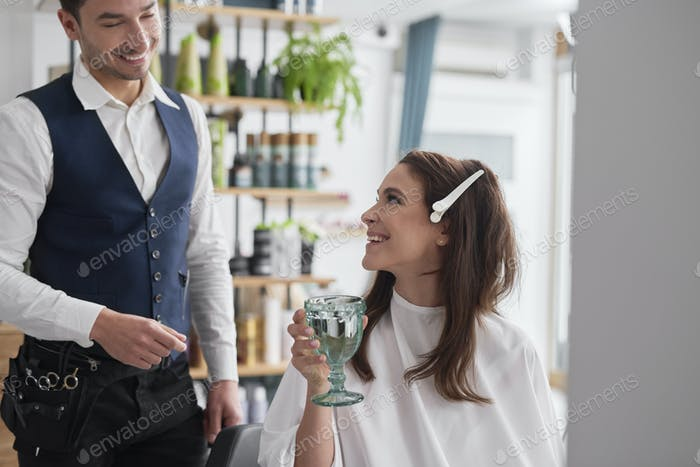 Happy hairdresser and customer are ready to change hairstyle