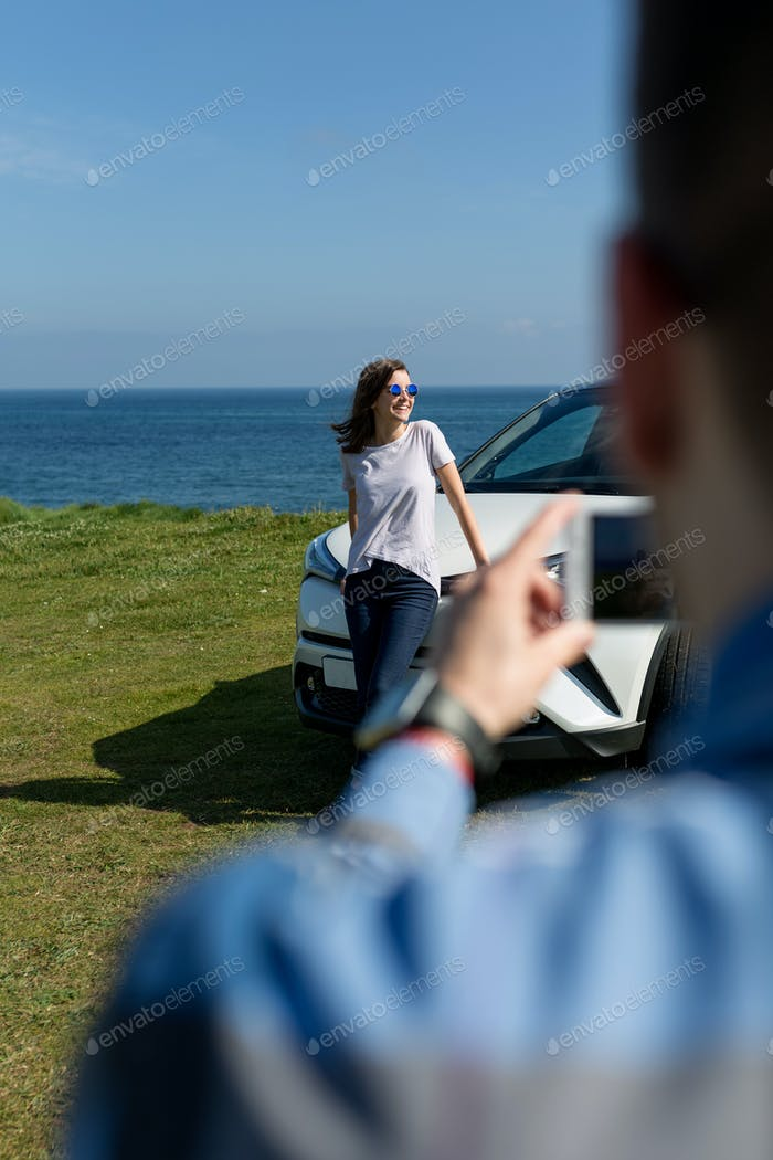 Guy taking picture of girl leaning on a car