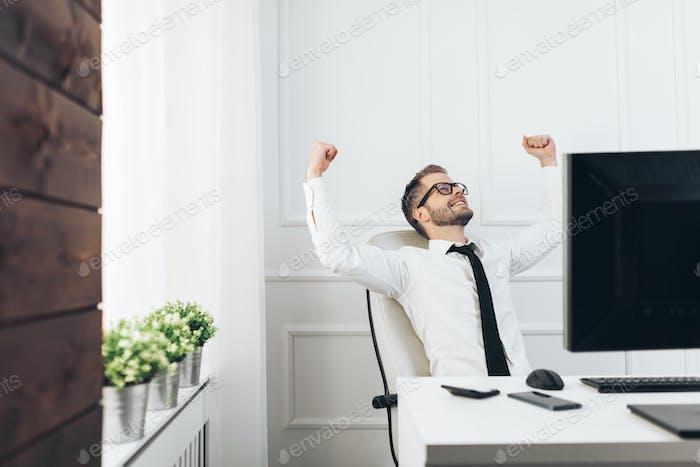 Erfolgreicher Geschäftsmann sitzt in seinem Büro