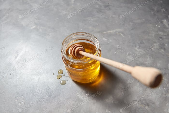 Glass pot with natural sweet honey and dipper on a gray stone kitchen table. Pure natural sweet