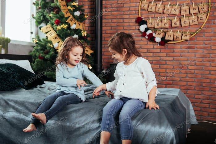 Kids sits on the bed with decorative background. Conception of new year