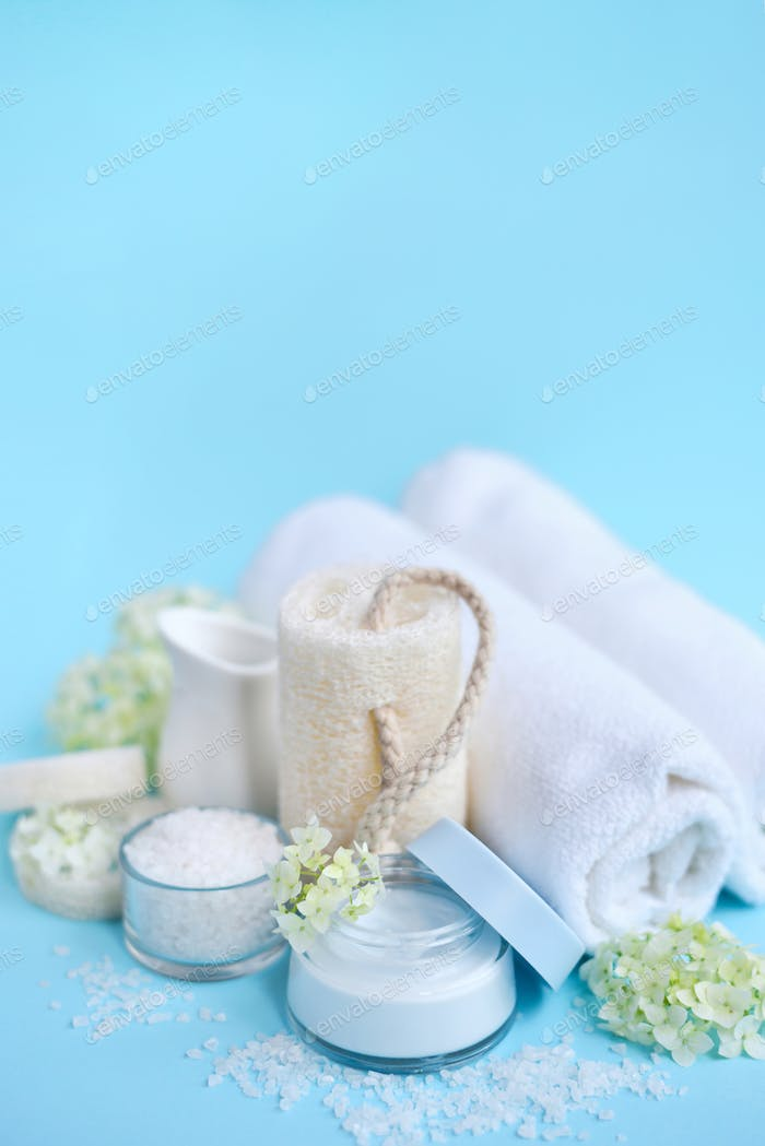 Spa composition with cream, salt, towel and flowers on a blue ba