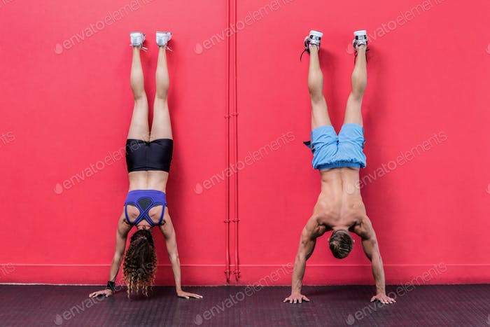 Muscular couple doing handstand exercises at the crossfit gym