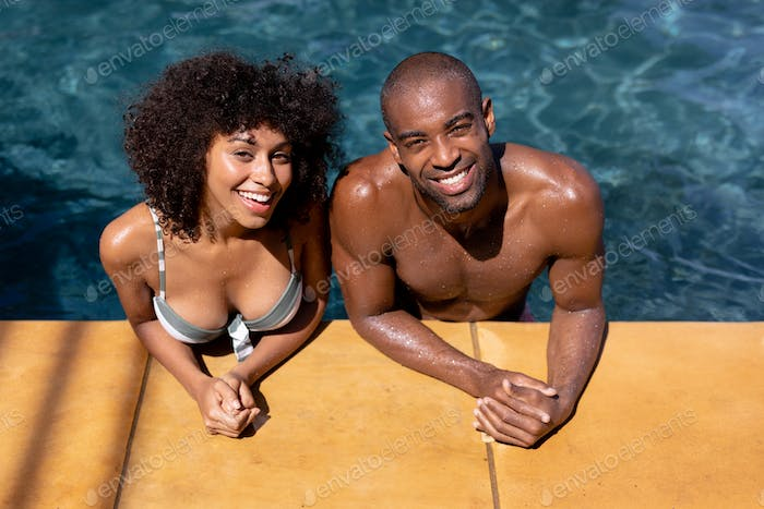 Happy young couple relaxing in the swimming pool