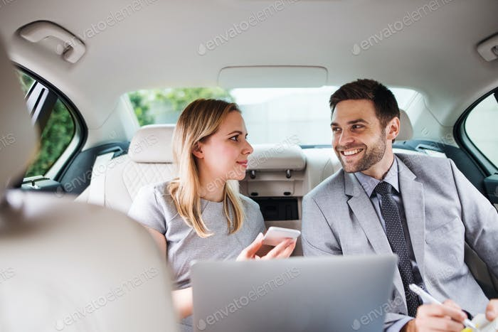 Business couple with laptop sitting on back seats in car, talking