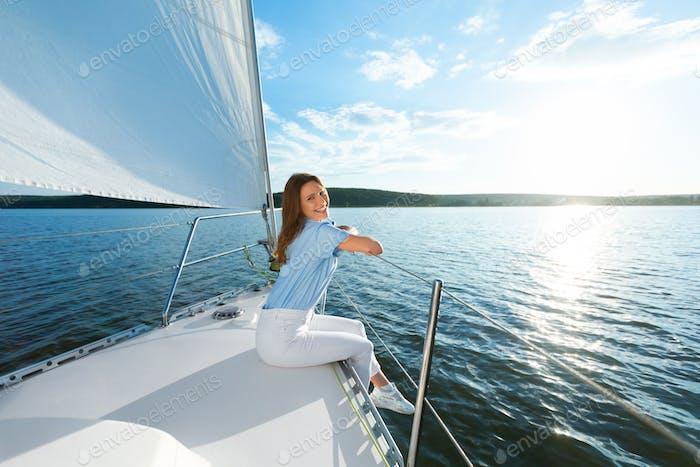 Happy Woman Sitting On Yacht Deck Enjoying Sea Ride Outdoors