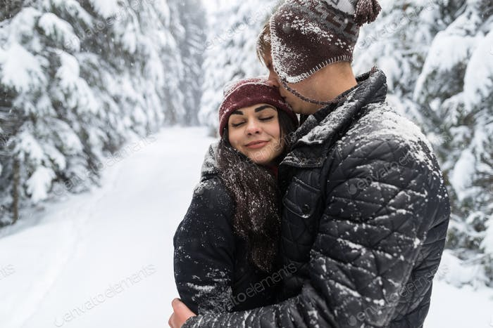 Young Romantic Couple In Snow Forest Outdoor Man And Woman Embrace
