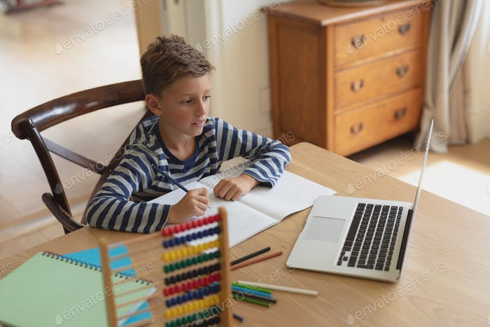 High angle view of Caucasian boy doing homework at table in a comfortable home
