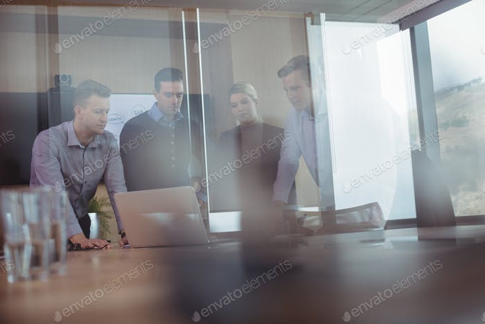 Business colleagues seen through glass discussing around desk during meeting