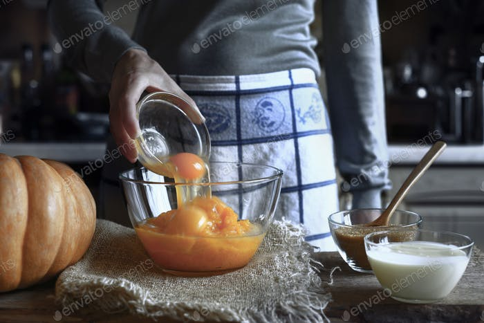 Adding eggs in the pumpkin puree in the glass bowl