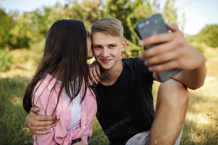 Young cool boy sitting on lawn in park and embracing girl while making selfie