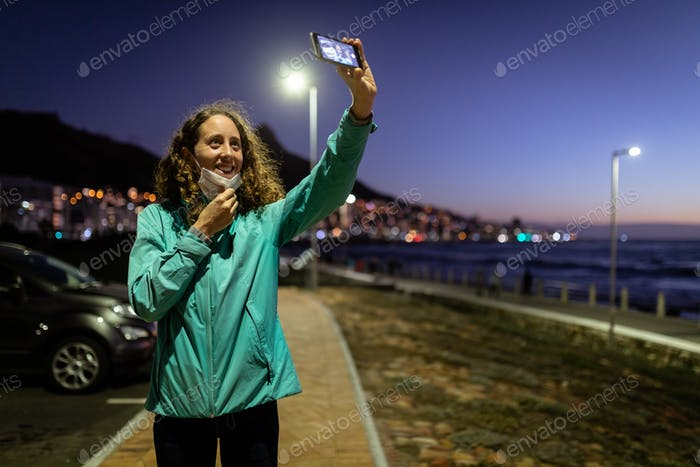 Caucasian woman putting off a protective mask, taking a picture in the streets