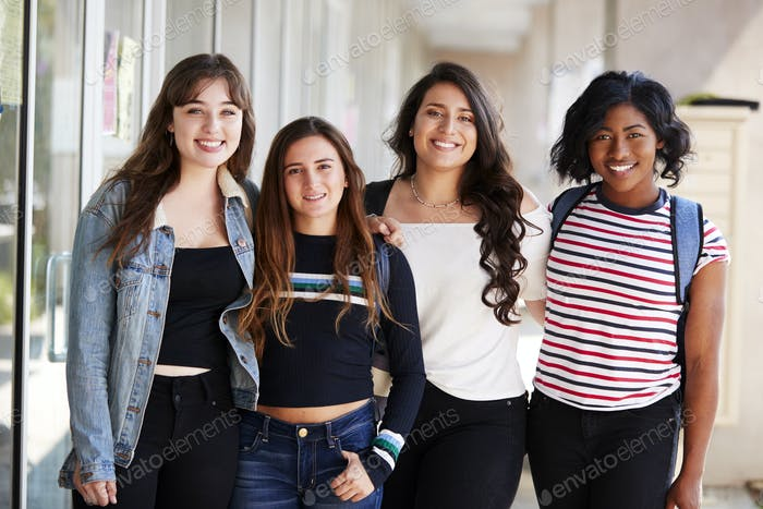 Portrait Of Smiling Female College Student Friends In Corridor Of Building