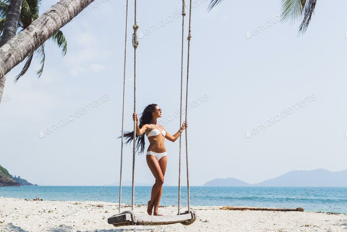Beautiful thin woman swinging on a swing on paradise beach with nobody
