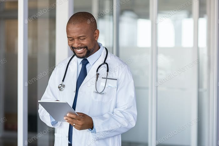 African doctor using digital tablet at hospital