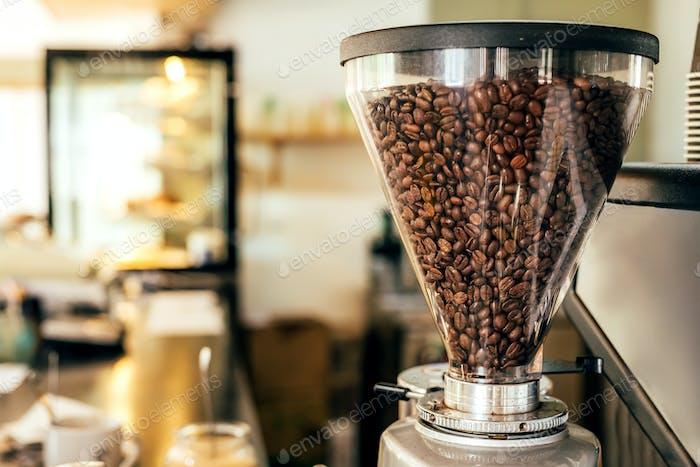 Kaffeebohnen in einem großen Glasmühle Maschinenhalter mit verschwommenem Hintergrund eines Cafés