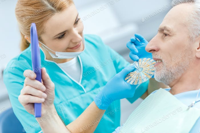 Professional dentist with samples comparing teeth of mature patient looking at mirror