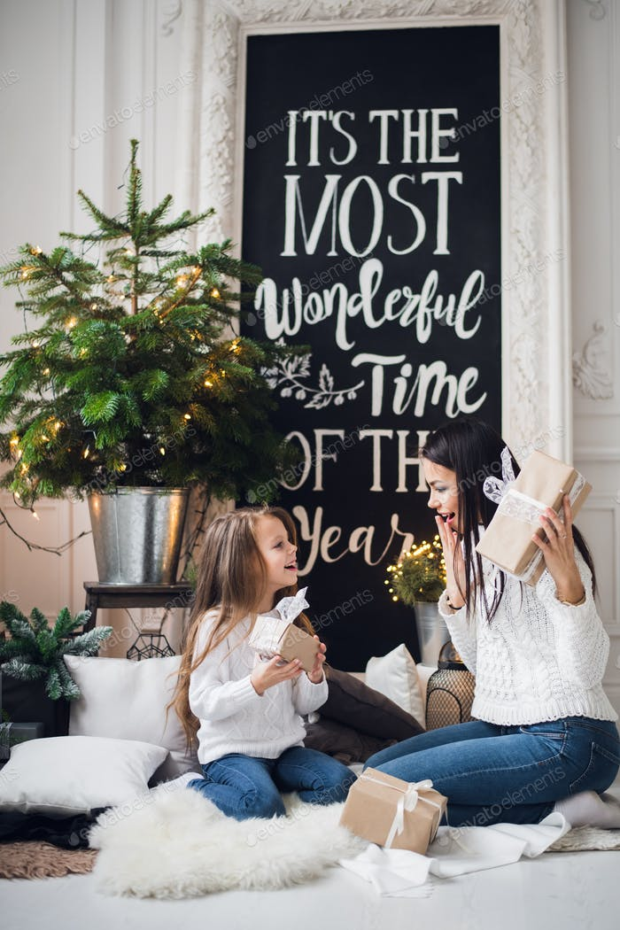 Merry Christmas and Happy Holidays. Cheerful mom and her cute daughter girl exchanging gifts. Parent