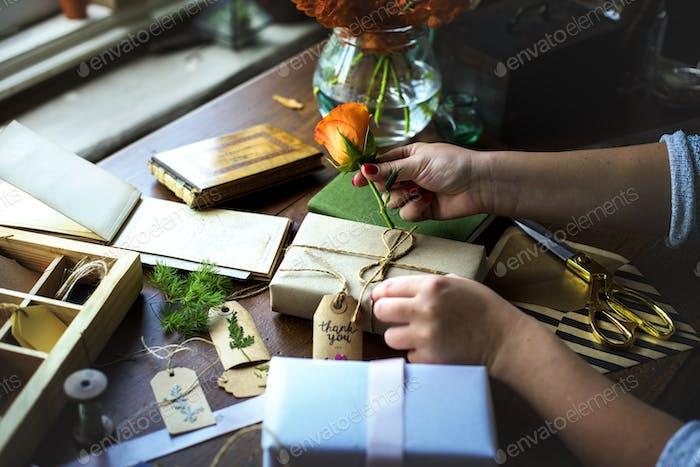 Hände DIY Wrapping Geschenk-Box auf Holztisch