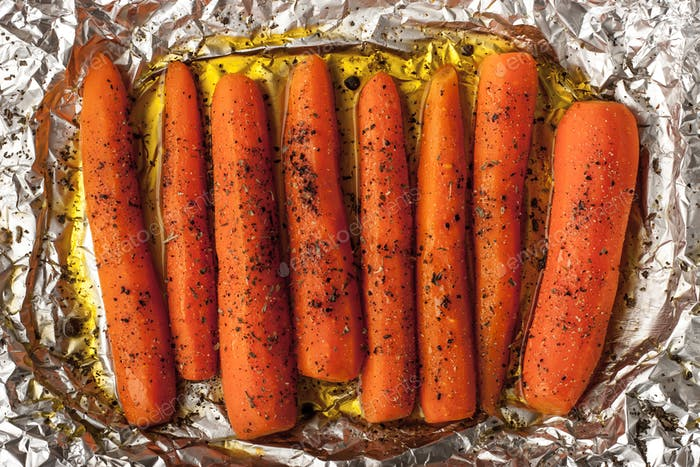 Baked carrots with black pepper on a sheet of foil top view