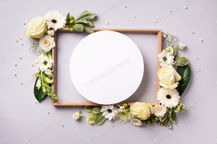White roses, lily, gerbera and circle shape paper over grey background. Flat lay, top view. Creative