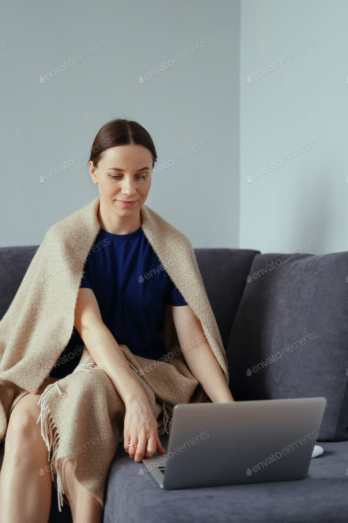 Young woman cuddling in a warm blanket with a laptop