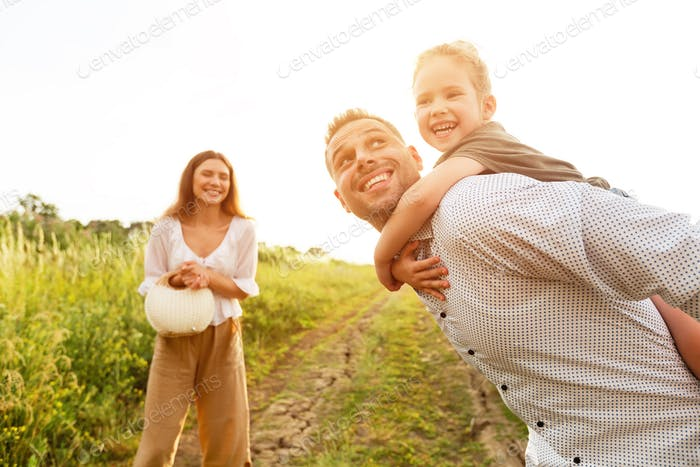 Young parent giving piggyback ride to his child
