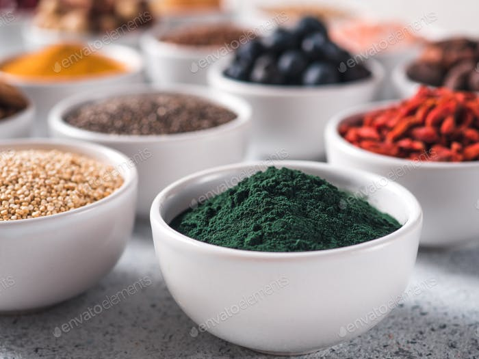 Spirulina in small white bowl and other superfoods