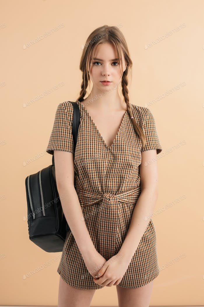 Young attractive school girl with braids in jumpsuit with backpack thoughtfully looking in camera
