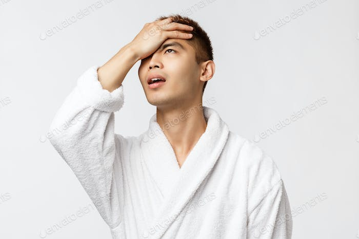 Beauty, spa and leisure concept. Portrait of upset, sighing and concerned asian man, facepalm