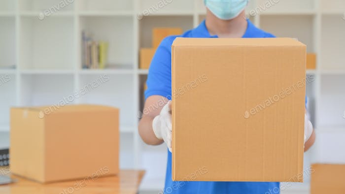 The delivery staff held a brown paper box. He was wearing gloves and a mask.