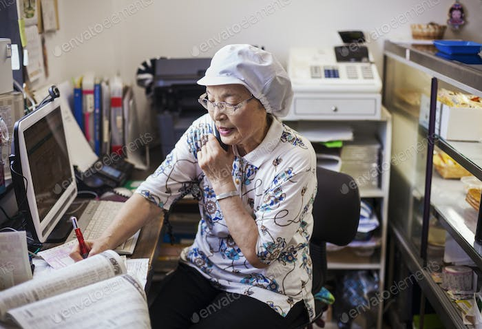 A mature woman at a desk in the office of a noodle production factory on the telephone.
