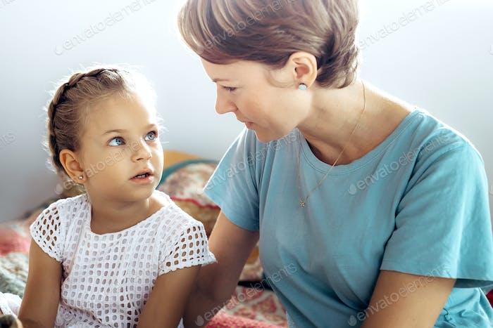 Mutter und ihre kleine Tochter sprechen auf dem Bett und schauen sich gegenseitig an