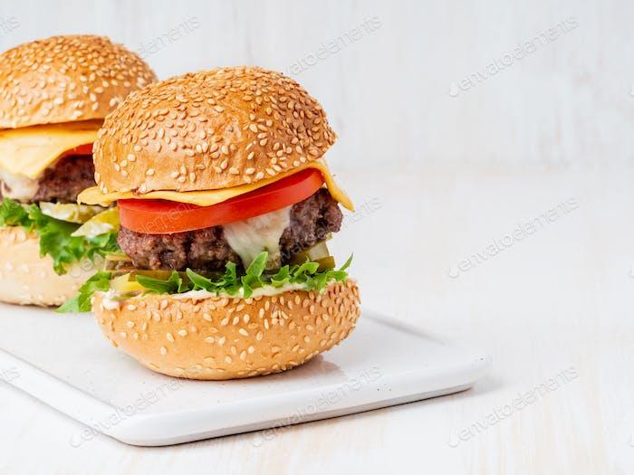 Zwei Hamburger auf weißem Hintergrund, heiße hausgemachte ungesunde Fettfutter, Kopie Raum
