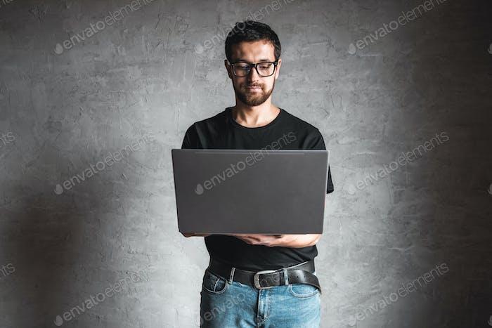 Mann in einem schwarzen T-Shirt mit einem Laptop auf einem grauen Hintergrund. Bildung, Erfolg, Wissen