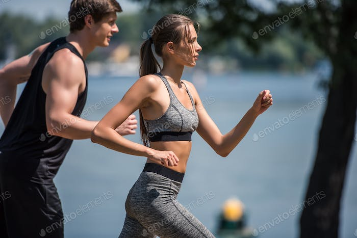 side view of young sportive couple jogging together in park
