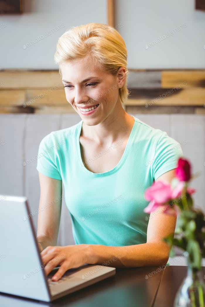 Happy pretty blonde using computer at the cafe