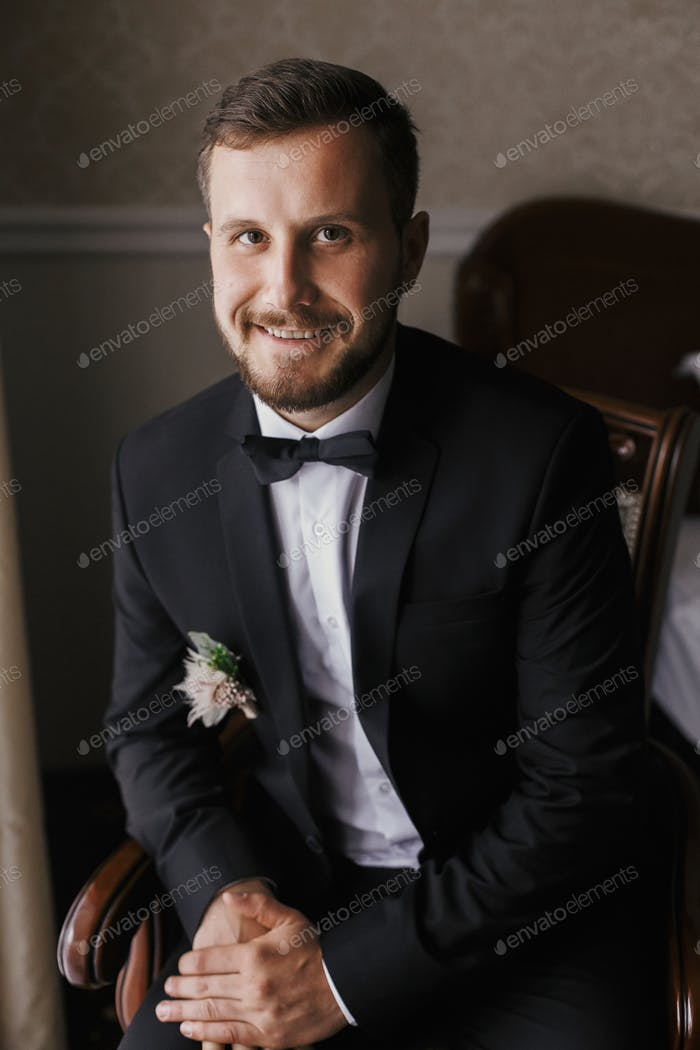 Stylish groom in black suit and bow tie, sitting in chair at window light