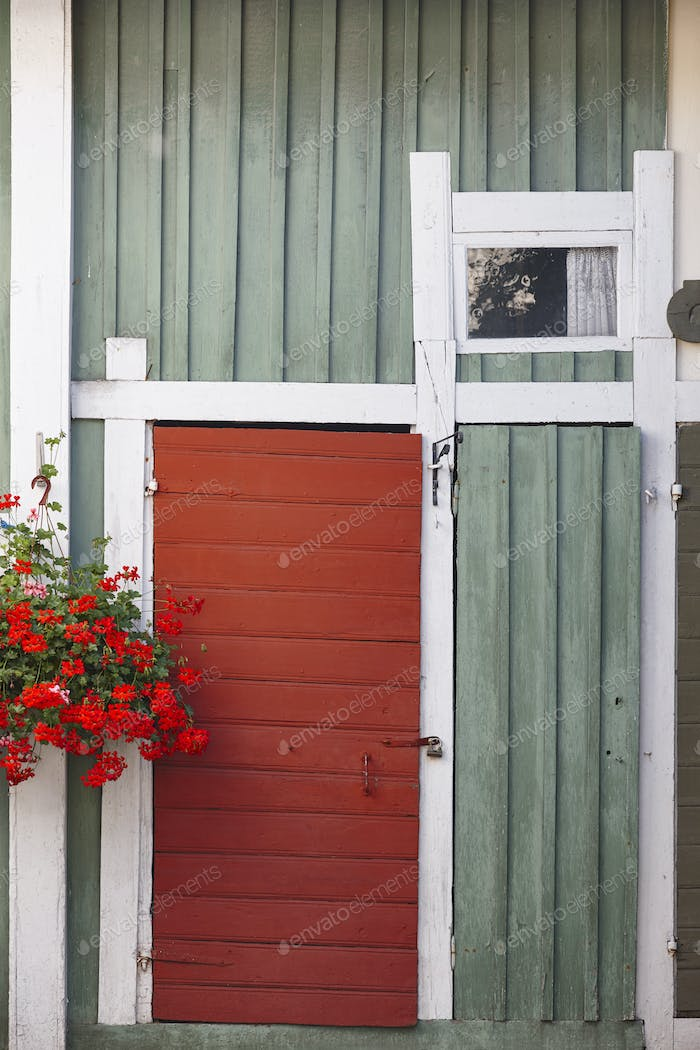 Traditional rusted finland wooden facade in green and red color